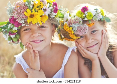 Two adorable little sisters wearing flowers crowns by warm and sunny summer day