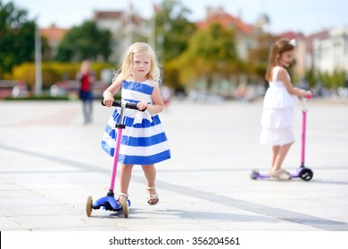Two adorable little sisters wearing beautiful dresses riding their scooters in a summer park