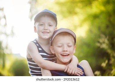 Two adorable  sibling boys hugging and having fun outdoors. Cute friends playing together on sunny warm summer day. Brother love.