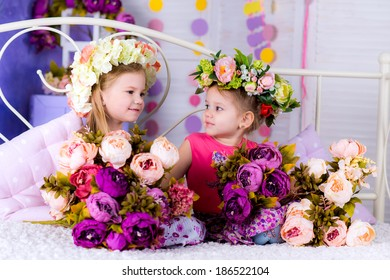 two Adorable smiling little girl with flowers on bed