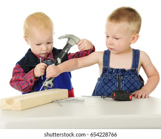 Two adorable toddler boys standing at a table with a short 2 x 4 board, nails, and tools.  One looks somewhat annoyed while the other puts a nail where he thinks it belongs  On a white background.