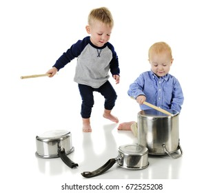 Two adorable toddlers playing drums on kitchen pots and pans. One is kneeling, playing a crock pot, the other is behind him with the drumstick ready for a major whack.  On a white background.