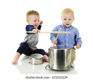 """Two adorable toddlers playing """"drums"""" together with drumsticks and upside down pots and pans.  On a white background."""