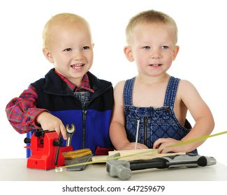 Two adorable toddlers standing at a tool bench with several toy tools, wooden boards and a large nail.  On a white background.