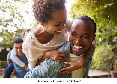Two adult black couples piggybacking looking at each other
