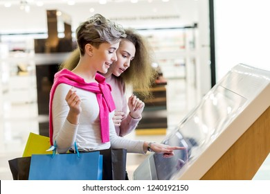 Two adult caucasian girlfriends use information kiosk at shopping center. Happy women with shopping bags pointing finger at the info desk. Consumerism, shopping, lifestyle concept