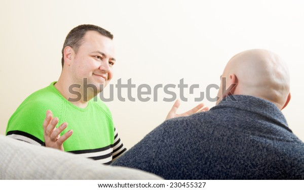 Two adult  friends  talking at home