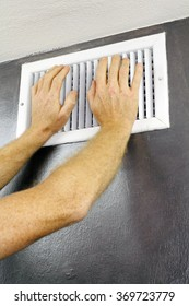 Two adult hands placed over an out air vent register of a central heating system on a gray wall near a white ceiling. A white metal air vent with two adult male caucasian hands on
