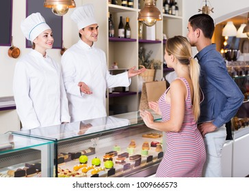 Two adult hospitable pastry chefs warmly greeting couple in pastry bar