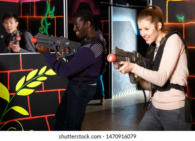Two adult laser tag players of different nationalities aiming laser guns at other players during lasertag game in dark room