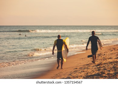Two adult males with their surfboards walk on the beach in the sand towards a great surf spot in Malibu, California during a gorgeous sunset.