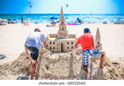 Two adult men build a sand castle on the beach