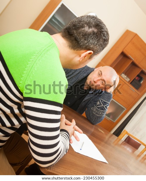 Two adult men discussing something at table