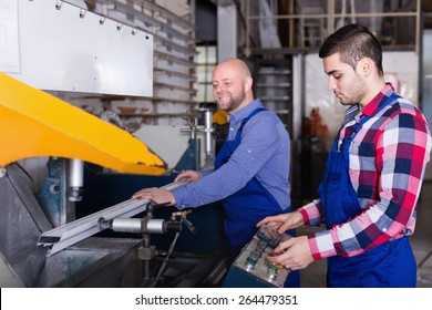 Two adult men in uniform working on machine in PVC shop