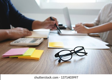 Two adult people working together with documents in library. Education concept.