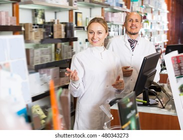 Two adult pharmacists wearing white coats standing next to shelves with medicine