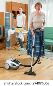 Two adult smiling women clean at home together