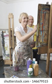 Two adult students painting at easel in art class