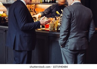Two adult successful businessmen discuss and talk about business deal in the bar while they drinking at the evening