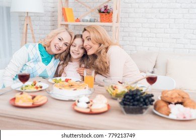 Two adult women and a girl are hugging, sitting at a table. This is the mother and grandmother of the girl. They have dinner at home.