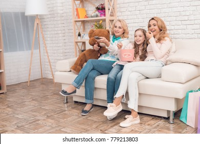 Two adult women and a girl are sitting on the couch and watching TV. They are in a good mood. They are smiling.