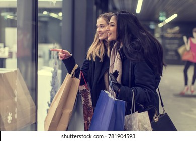 two adult women on their midnight shopping spree in a beautiful city center, heavy loaded with christmas gifts,  shopping, while walking along store windows.