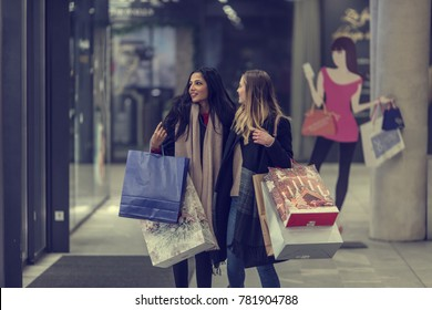 305819f46 two adult women on their midnight shopping spree in a beautiful city  center, heavy loaded
