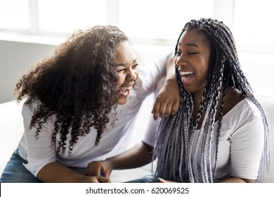 Two affectionate friends afro american sitting on sofa