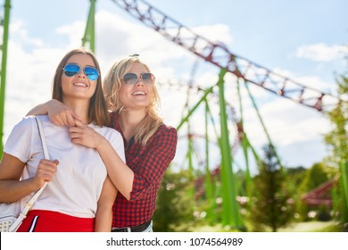 Two affectionate girls in sunglasses looking at one of amusements while spending time in theme park on summer weekend