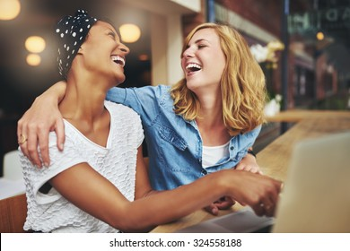 Two affectionate multiracial women friends hugging and laughing as they point at a laptop computer screen that they are sharing