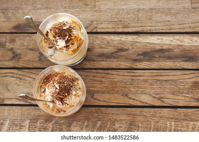 Two affogato on a wooden table. Delicious espresso dessert with ice cream in a glass. Copy space. Atmosphere of summer holidays, siesta, coffee breaks