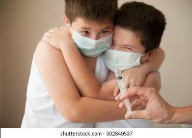 two afraid brothers in a surgical mask looking at hand with syringe