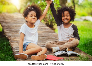 Two African American Afro children together in the garden. Happy young little boy and girl in the park.