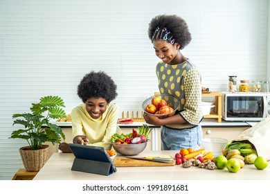 Two African american children enjoy cooking together in modern kitchen, Two brethren happy make fruit and vegetable salads from Video tutorial from tablet. Learn cook homemade from video call