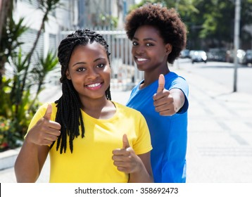 Two african american girlfriends showing thumb up