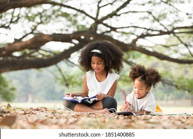 Two African American little girl using pencil writing and doing homework on notebook together in the park. Happy two kids girl drawing on notebook with pencil while sitting and lying on mat outdoor