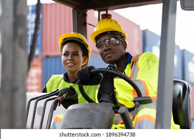 Two African American male and female worker in uniform and helmet driving and operating on diesel container forklift truck at commercial dock site. Multicultural worker