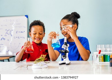 Two African American mixed kids testing chemistry lab experiment and holding glass tube flask along with microscope on table and smile in science classroom - fun learning education concept