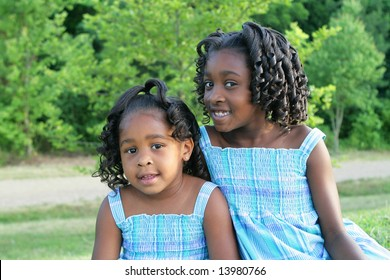 Two african american sisters playing in a park