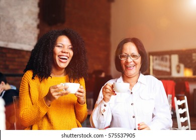 Two African american woman drinking coffee.