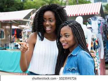 Two african american woman shopping at typical market