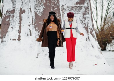 Two african american womans in sheepskin and fur coat posed at winter day against snowy background with cups of coffee.