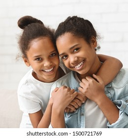 Two african beautiful sisters hugging each other, white background
