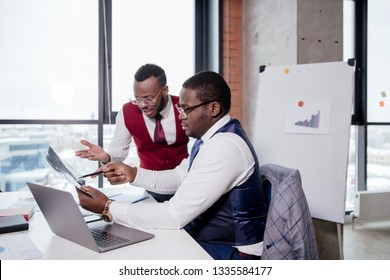 Two African businessmen discussing documents sitting at a table in the office