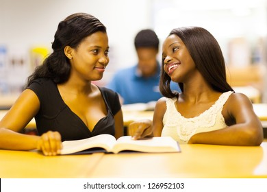 two african college girls reading book in library