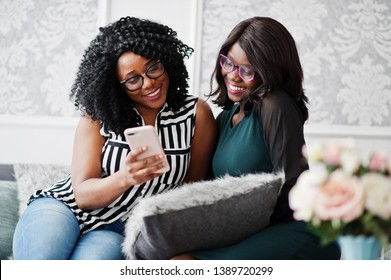 Two african woman friends wear on eyeglasses sitting at couch indoor white room and looking at mobile phone.