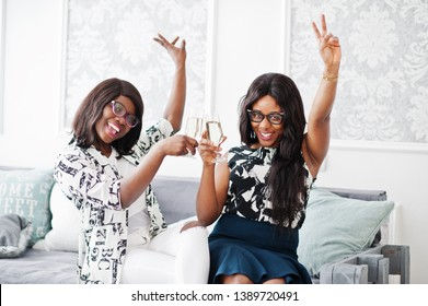 Two african woman friends wear on eyeglasses posed indoor white room and clink with champagne glasses.