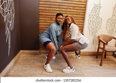 Two african womans in stylish casual clothes posing against wooden wall sat down and dance twerk.