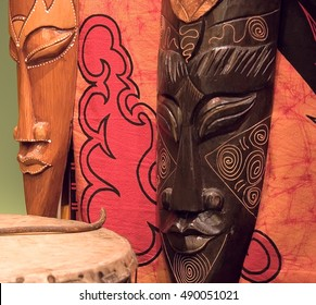 Two african wooden masks, tomtom and red painted fabric.