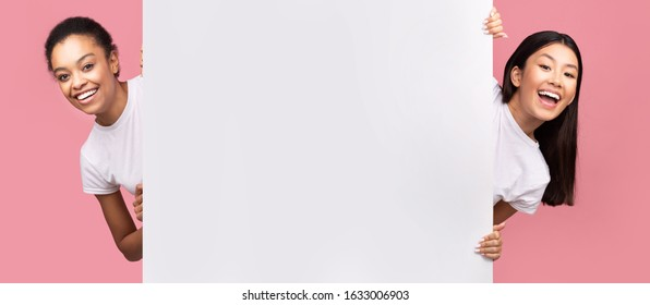 Two Afro And Asian Girls Peeking Out Of Blank White Board Smiling To Camera Posing Over Pink Studio Background. Panorama